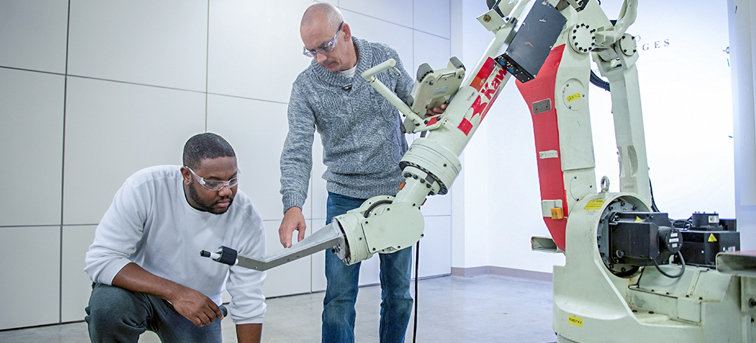 Student and instructor examining robotic arm