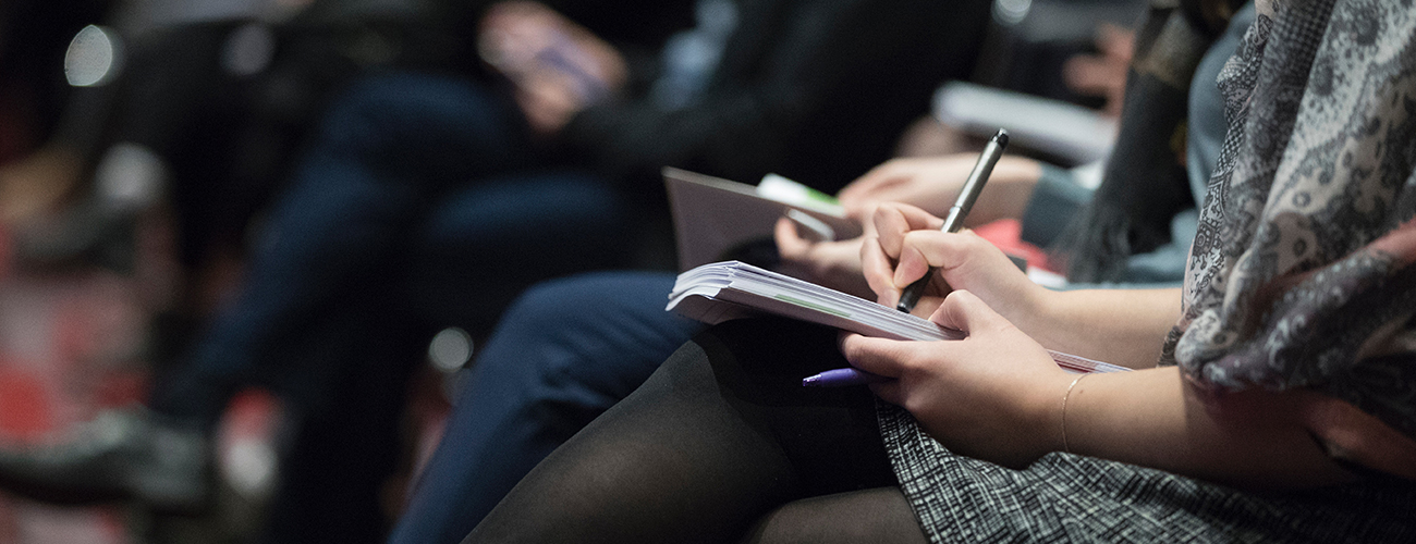 Woman writing notes during conference