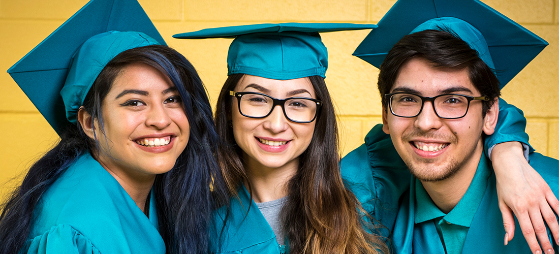 Photo of three students in graduation cap and gown