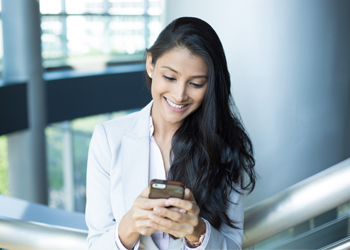Hispanic business woman looking at cellphone